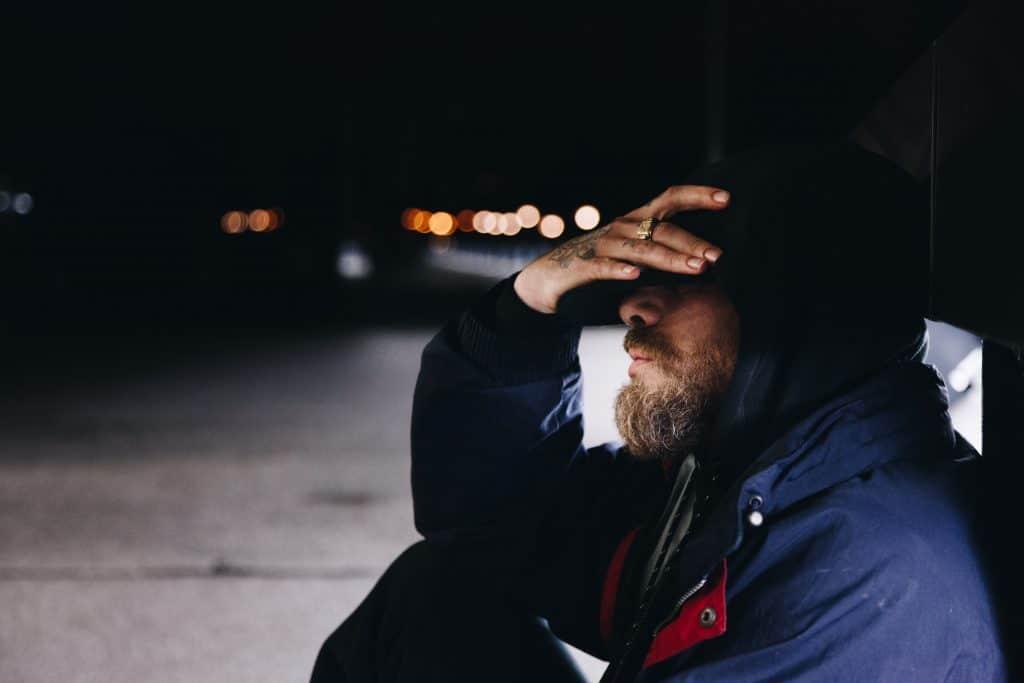 Man Thinking on the Sidewalk in the Dark
